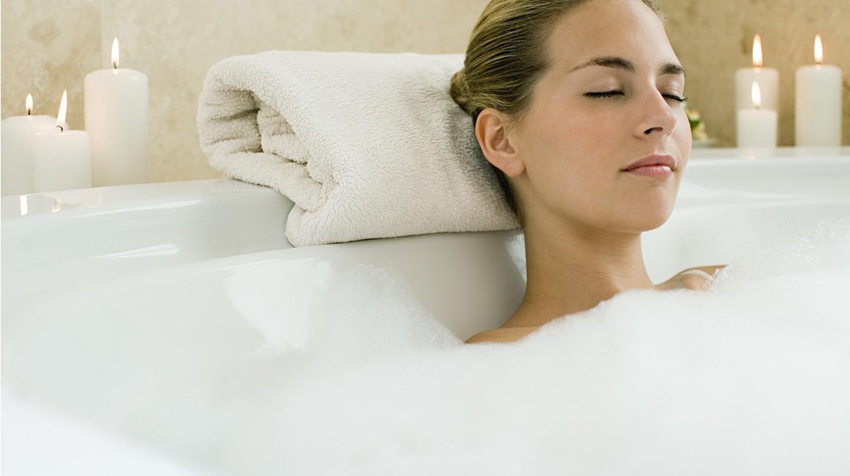 Wellness zu Hause: Eine Frau liegt mit geschlossenen Augen in einer Badewanne mit viel Schaum.