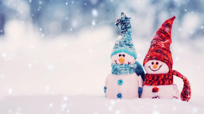 Frohe Weihnachten: Zwei gehäkelte lächelnde Schneemänner mit blauen bzw. roten Schals und Mützen in Schneelandschaft.